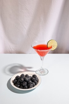 Platte von blauen beeren mit cocktailgetränk über weißem schreibtisch
