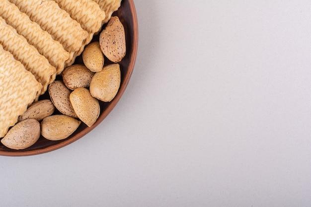 Platte von geschälten organischen mandeln und keksen auf weißem hintergrund. hochwertiges foto