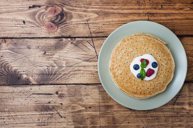 Platte von köstlichen dünnen pfannkuchen mit beeren auf holztisch