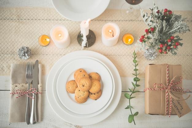 Platte von plätzchen und geschenk auf abendtische mit weihnachtsdekorationen