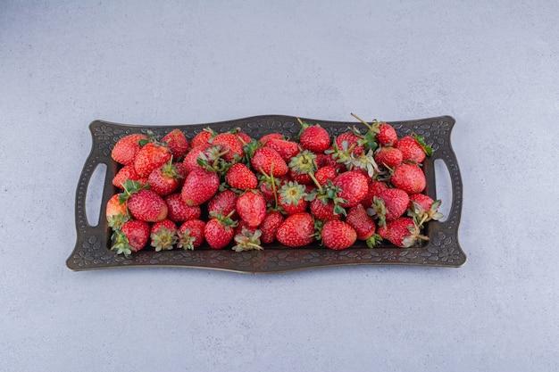 Platte von saftigen erdbeeren auf marmorhintergrund.