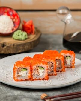 Platte von sushirollen mit lachsen, gurke bedeckt im roten tobiko