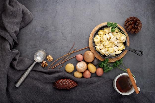 Platte von tortellini und von pilzen auf einem grauen hintergrund