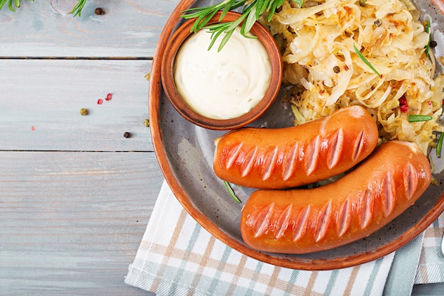 Platte von würsten und von sauerkraut auf holztisch. traditionelles oktoberfest-menü. flach liegen. ansicht von oben.