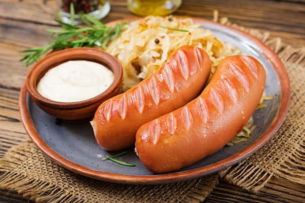Platte von würsten und von sauerkraut auf holztisch. traditionelles oktoberfest-menü