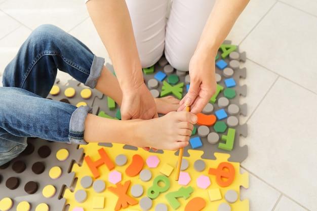 Plattfußbehandlung für kinder mit speziellem massageteppich. kleines mädchen auf massagematte, das übungen zur vorbeugung von plattfüßen macht. fußstärkungsübungen. podologie-klinik.