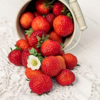Platz. erdbeeren auf einem weißen hölzernen alten hintergrund, gestrickte serviette