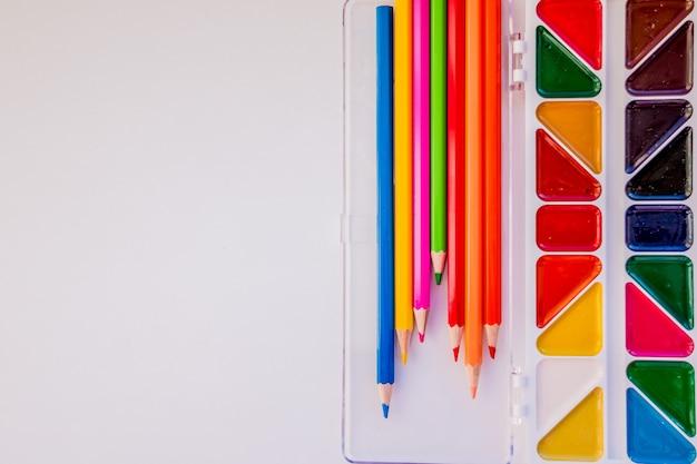 Platz für text, design. der arbeitsbereich des künstlers zum zeichnen. farbstifte, aquarell, farben, weißes papier lokalisiert auf hintergrundtabelle. bildungskonzept.