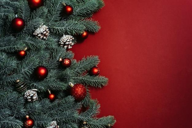 Platz für text zwischen weihnachtsbaumzweigen mit weihnachtsdekorationen und kugeln auf einem roten hintergrund. weihnachtskomposition.