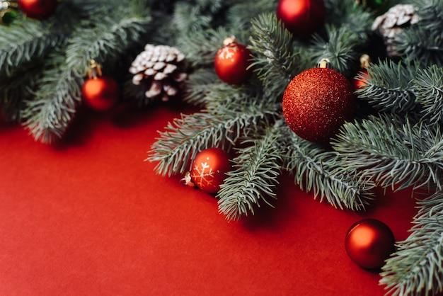 Platz für text zwischen weihnachtsbaumzweigen mit weihnachtsdekorationen und kugeln auf einem roten hintergrund.