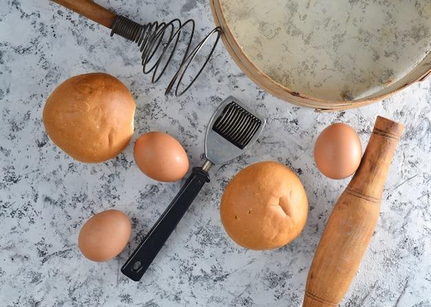 Platz zum kochen. küchenutensilien und zutaten zum kochen auf einem weißen betontisch. brötchen, sieb, schneebesen, nudelholz, eier. draufsicht.