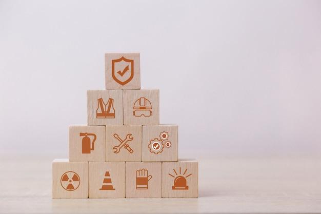 Platziere holzklötze auf der pyramide. 100 prozent arbeitssicherheitskonzept.