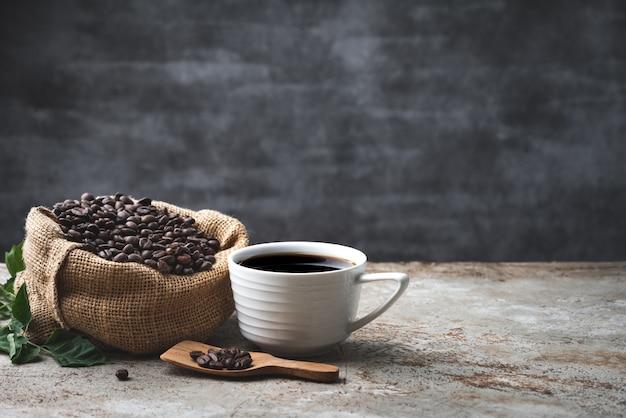 Platzieren sie schwarzen kaffee und bohne im sacknahrungsmittelhintergrund Premium Fotos