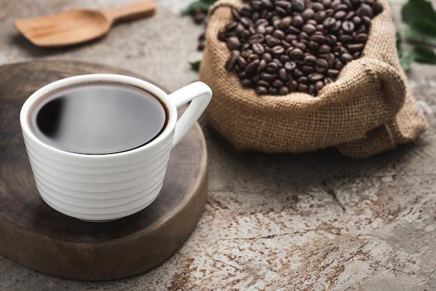 Platzieren sie schwarzen kaffee und bohne im sacknahrungsmittelhintergrund