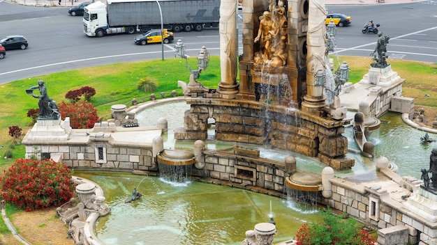 Plaza de espana, das denkmal mit brunnen und skulpturen in barcelona, spanien. der verkehr