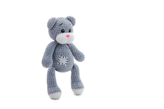 Plüsch gehäkeltes graues bärenspielzeug mit aufnäher steht auf weißer oberfläche