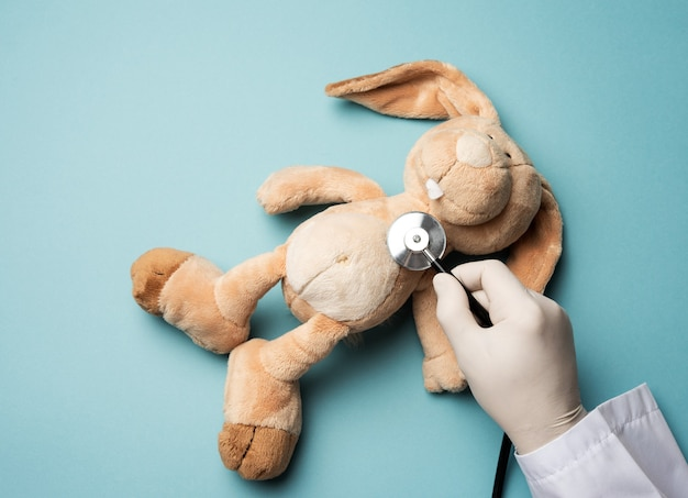 Plüschkaninchen liegt auf einer blauen oberfläche, eine männliche hand in einem weißen latexhandschuh hält ein medizinisches stethoskop, draufsicht, pädiatrie