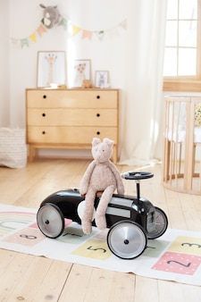 Plüschkaninchen sitzt im weinleserennwagen der kinder im kinderzimmer. skandinavisches interieur. retrostilbabyauto im schlafzimmer der kinder. spielzeug für ein kind im kindergarten. rustikal. hygge