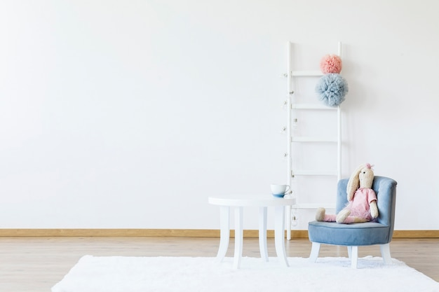 Plüschtier auf grauem stuhl am weißen tisch in minimalem kinderzimmer mit kopierraum. echtes foto