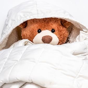 Plüschtier in der großen weißen jaket des kindes gekleidet. weicher teddybär für winter- oder herbstkälte. liebe und fürsorge, kuschelig für kinderzimmer.