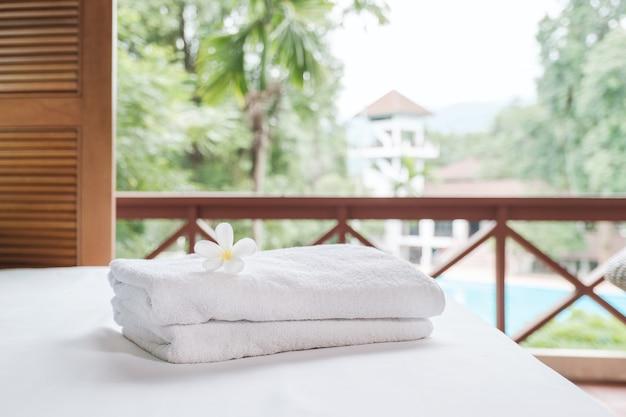 Plumeria und handtücher auf dem bett im luxuriösen hotelzimmer bereit für touristische reisen.
