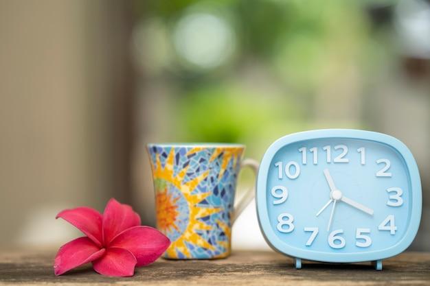 Plumeria wecker und tasse kaffee mittagspause konzept