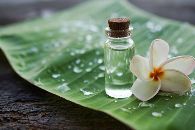 Plumeriaöl in der glasflasche mit plumeriablume auf bananenblatt