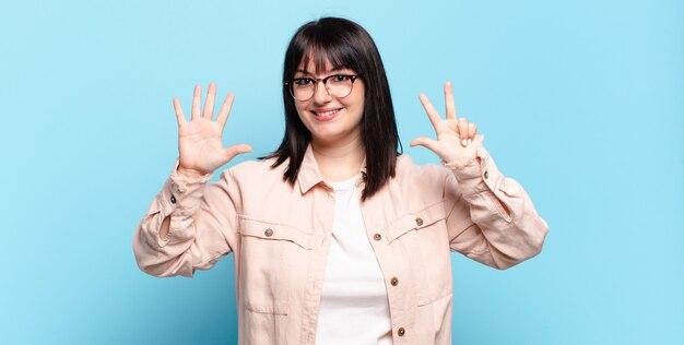 Plus größe hübsche frau lächelnd und freundlich aussehend, zeigt nummer acht oder acht mit der hand nach vorne, countdown