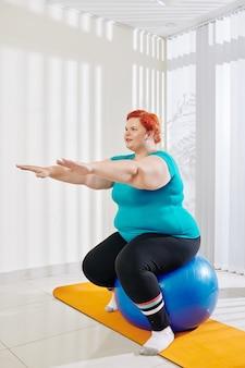Plus size frau balanciert auf fitnessball