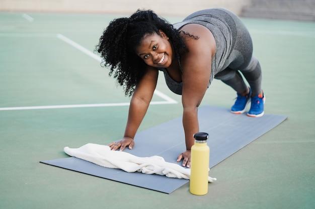 Plus-size-frau macht trainingsroutine im freien im stadtpark