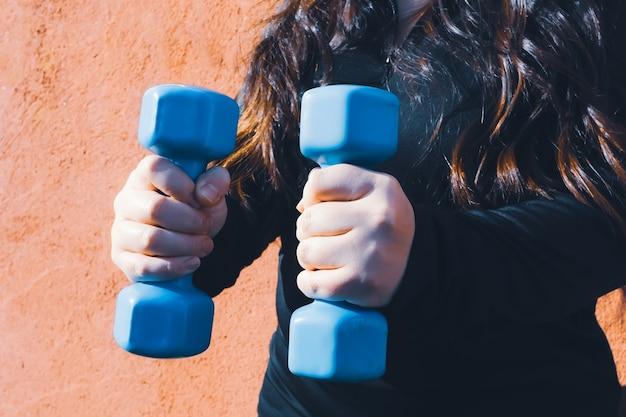 Plus-size-frau mit zwei blauen hanteln gesundes leben fitness-konzept