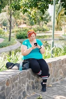 Plus size frau prüft smartphone