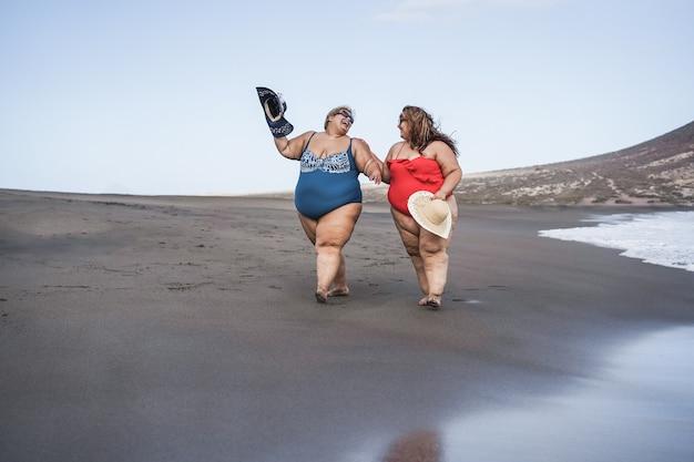 Plus size frauen, die am strand spazieren gehen und spaß während der sommerferien haben