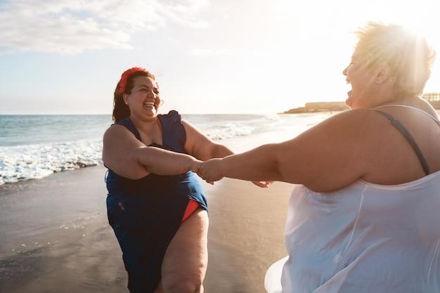 Plus size frauen tanzen am strand spaß in den sommerferien - kurvige frau zusammen lachen - übergewicht körper und glück konzept - fokus auf das gesicht der rechten frau