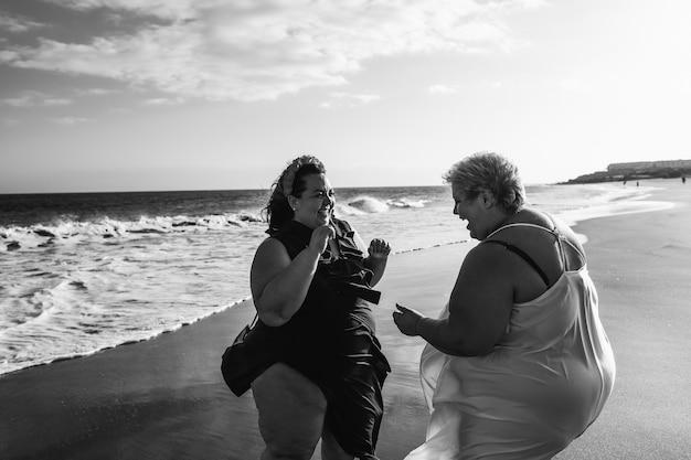 Plus size frauen tanzen am strand spaß in den sommerferien - kurvige frau zusammen lachen - übergewicht körper und glück konzept - schwarz-weiß-bearbeitung