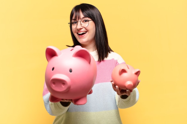Plus size hübsche frau mit einem sparschwein. einsparungskonzept