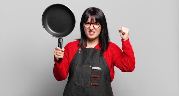 Plus size hübsche kochfrau, die mit einer pfanne kocht