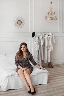 Plus size model girl in einem modischen kleid in einem schlafzimmer interieur. junge pralle frau mit hellem make-up und mit stilvoller frisur, die im innenraum aufwirft. xxl mode. körper positiv