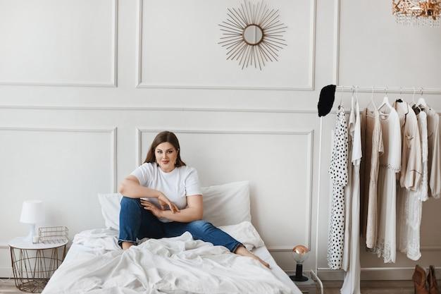Plus-size-modell mädchen in jeans und weißem t-shirt sitzen auf dem bett in der nähe von kleiderbügel mit kleidung. junge lächelnde pralle frau, die eine entscheidung trifft, was zu tragen. xxl mode