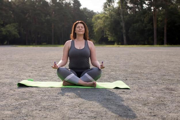 Plusgrößenmädchen, das draußen yoga meditiert