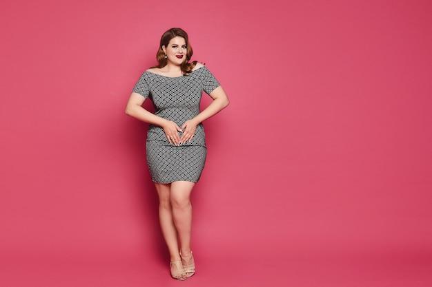 Plussize model girl mit hellem make-up und stilvoller frisur in einem kurzen kleid