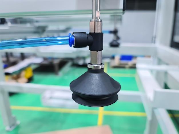 Pneumatischer faltenbalg-saugnapf in der werkstatt an den blauen schlauch angeschlossen
