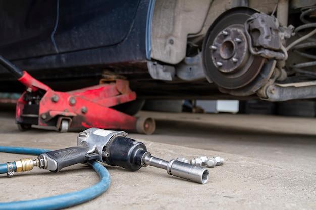 Pneumatisches schraubenschlüsselwerkzeug auf dem asphalt und ein wagenheber zum anheben der karosserie und zum reifenwechsel.