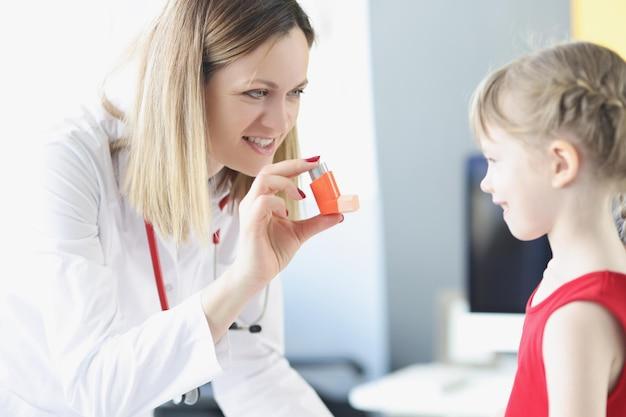 Pneumologe arzt hält hormoninhalator vor kleinem mädchen in der klinikdiagnostik und