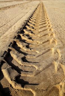 Pneus-fußabdruck der traktorreifen auf strandsand gedruckt