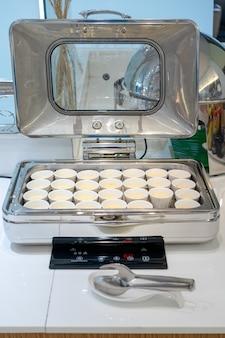 Pochierte eier in der großen weißen quadratischen schüssel bei thailand resort.