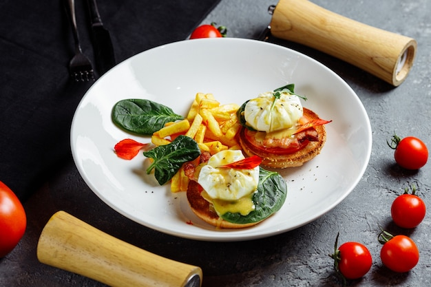 Pochierte eier mit pommes frites und speck auf toast.