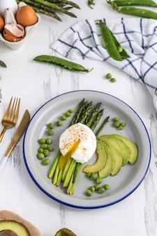 Pochierte eier mit spargel, avocado und erbsen