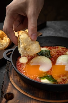 Pochierte eier mit tomaten und sauce in einer pfanne auf einem holzbrett
