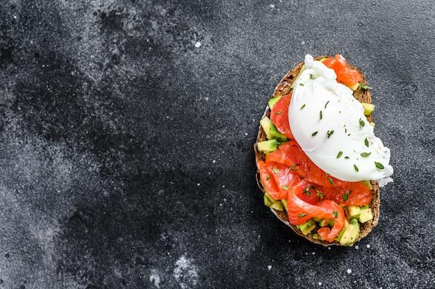 Pochiertes ei auf gegrilltem toast mit räucherlachs und avocado